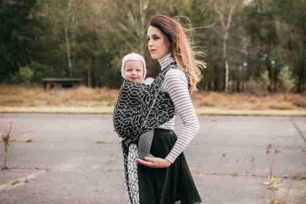 Vrouw met baby in zwarte draagdoek