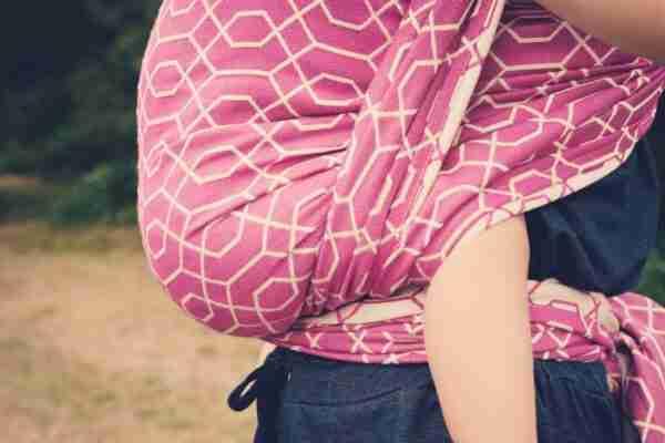vrouw met bruin lang haar draagt roze draagdoek waar kindje in zit